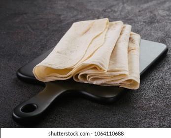 Armenian flat bread lavash. Pita bread on black cutting board over black cement background. Copy space.