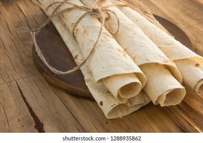 Armenian flat bread lavash. Pita bread on wooden cutting board