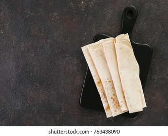 Armenian flat bread lavash. Pita bread on black cutting board over black cement background. Copy space. Top view or flat-lay.
