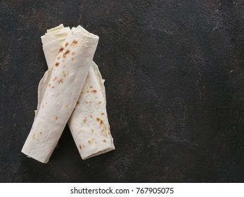 Armenian flat bread lavash. Pita bread on black cement background. Copy space. Top view or flat-lay.