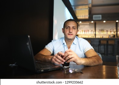 Armenian handsome man working behind laptop in cafe