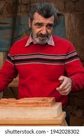 Armenian khachkar workshop, Yerevan, Armenia, October 2012: Portrait of a  crafts-man next to Armenian khachkar at his famous workshop in Yerevan.