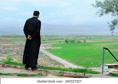 Armenian priest overlooking scenic fields and mountains