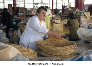 Armenian woman selling flat lavash bread, Yerevan, Armenia, October 2012: An Armenian woman keeps flat lavash bread moisturised dropping water drops on it at her stand in Yerevan Central Food Market