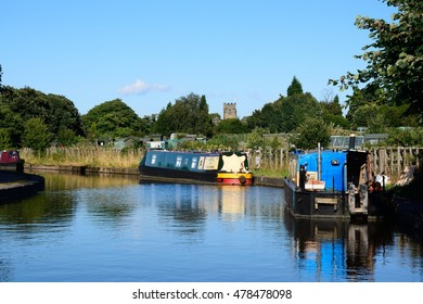 ARMITAGE, UNITED - AUGUST 8, 2016 - Narrowboats moored on the canal with allotments and church to the rear, Armitage, Staffordshire, England, UK, Western Europe, August 8, 2016.