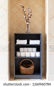 An armoire decorated with a branch of cotton, white towels and rows of toilet papper
