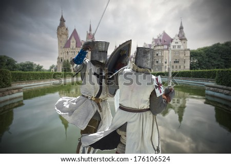 Armored fighting knights with medieval castle in the background, Moszna, Poland