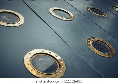 Armored portholes of brass with brass screws. A military ship of the early 20th century. Background for steampunk scene.