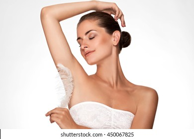 Armpit epilation, hair removal. Young woman holding her arms up and showing clean underarms, depilation smooth clear skin . Beauty portrait. armpit's care. Large white feather near  skin
