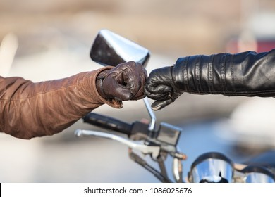 Arms of bikers touching with fists for greeting gesture, close-up view