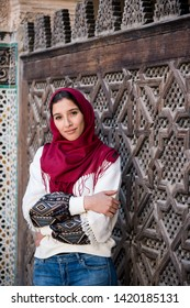 Arms crossed muslim woman in traditional clothing with red hijab and jeans in front of traditional arabesque decorated wall