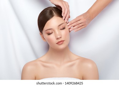 arms doing massage for beautiful woman with her eyes closed, pretty girl receiving facial treatment, skincare for attractive female