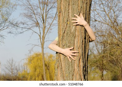 Arms embracing tree - concept of human care for nature preservation