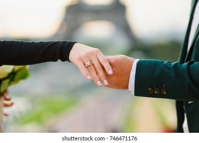 Arms and engagement ring with the Eiffel tower background. Engagement in Paris