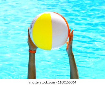 Arms holding the beach ball in a swiming pool
