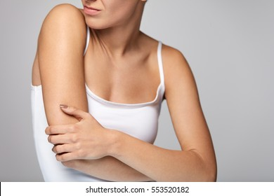 Arms Pain. Beautiful Woman Suffering From Painful Feeling In Arm Muscles. Closeup Of Female Body Feeling Pain In Shoulders, Touching Injured Arm With Hand. Injury, Health Care Concept. High Resolution