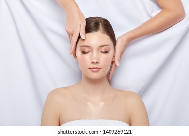 arms touching woman's face on white background, massage theraphy for head and face, person lying down in spa, women treatment
