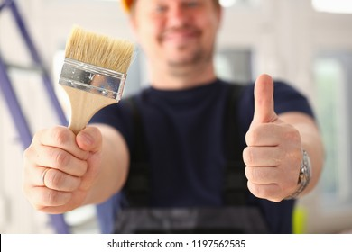 Arms of worker hold paint brush and show confirm sign with thumb up closeup. Manual job DIY inspiration joinery startup idea fix shop hard hat industrial education profession career concept