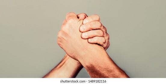 Arms wrestling. Friendly handshake, friends greeting, teamwork, friendship. Handshake, arms, friendship Man hand Two men arm wrestling
