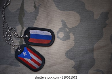 army blank, dog tag with flag of russia and puerto rico on the khaki texture background. military concept