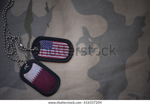 army blank, dog tag with flag of united states of america and qatar on the khaki texture background. military concept