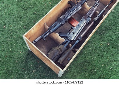 army box of ammunition with AK47 rifle and ammunition. An automatic weapon with a sniper scope in wood box