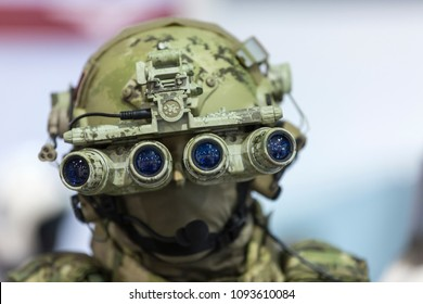 Army combat helmet are on, his face closed by using optical sights and night vision
