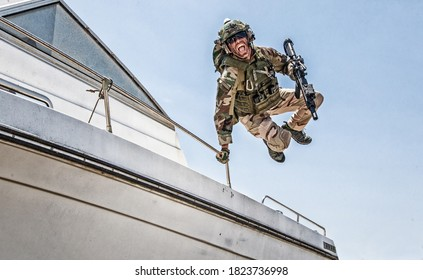 Army commando, special forces soldier equipped with body armour and battle helmet with radio headset, screaming and yelling while jumping from speed boat deck, landing on shore with assault rifle