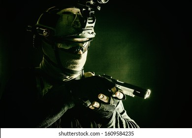 Army counter-terrorism squad, police SWAT team fighter hiding identity behind mask and glasses, wearing helmet with night vision-device, creeping in darkness, aiming service pistol during mission