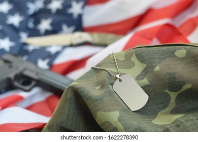 Army Dog tag token with 9mm bullets and pistol lie on folded United States flag and camouflage uniform