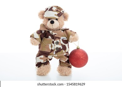 Army, military at Christmas concept. Cute teddy bear in soldier uniform holding a red christmas ball standing isolated against white background