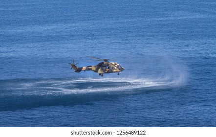 Army Military Rescue helicopter performing training rescue operation at sea. Helicopter drops divers soldiers during search and rescue operation.