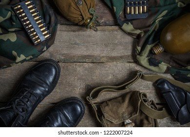 Army military uniform, weapon, holster, pistol, flask, boots on wooden background. Flat lay top view with copy space.Military background