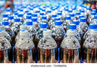 army of plastic bottles with black liquid and navy blue corcs stand in strong rows at shop and wait for buyers. Many bottles with pepsi top view. background made by big pepsi bottles