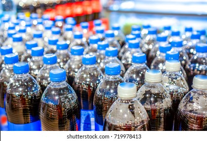 army of plastic bottles with black liquid and navy blue covers stand in strong rows at shop and wait for buyers. Many bottles with pepsi top view. background made by big pepsi bottles