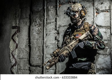 Army Ranger moving along the concrete wall on mission