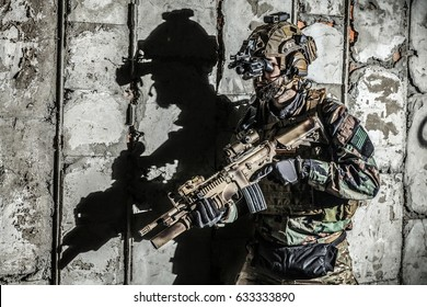 Army Ranger moving along the concrete wall with his black shadow