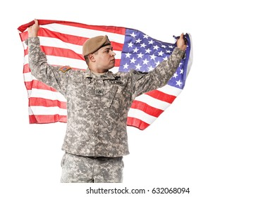 Army Ranger from Special Troops Battalion in universal Camouflage pattern Uniforms and Tan beret with Ranger Regiment crest standing and holding waving US flag in his hands proudly. National holidays