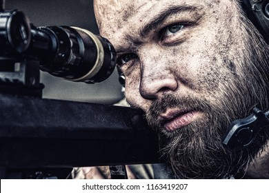 Army sniper with bearded, dirty face aiming with optical telescopic sight on sniper rifle, observing battlefield from ambush and searching targets to shoot, shooting on long range distances, close up
