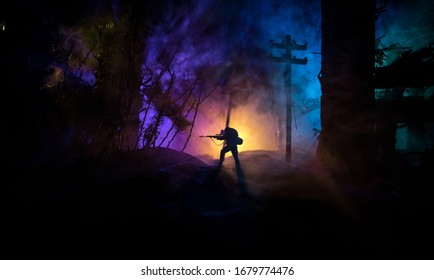 Army sniper with large caliber rifle standing in the fire and smoke. War Concept. Battle scene on war fog sky background, Fighting silhouettes Below Cloudy Skyline at night. City destroyed by war