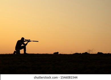 Army sniper with large-caliber sniper rifle seeking killing enemy. Silhouette on sky background.
