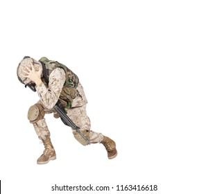 Army soldier in camo uniform, armed with assault rifle and machine gun, crouching to ground, holding helmets and covers ears with hands isolated on white studio shoot Grenade or bomb explosion