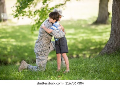 Army soldier embracing boy in park on a sunny day