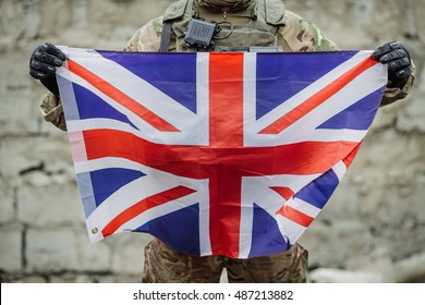 Army soldier holding British flag