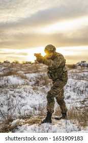 army soldier Man in the winter multicam camouflage is patrolling or patrol field territory wit gun. commandos with full equipment helmet and gun watch battlefield. Modern army soldier opposite the sun