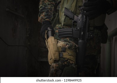 Army soldier pulls a gun weapon from his holster.