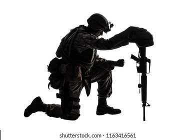 Army soldier in sorrow for fallen comrade, standing on knee, leaning on rifle with helmet and two dog tags on chain, studio shoot isolated on white low key silhouette. Military funeral honors, grief