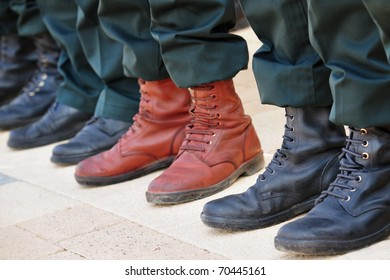 An army soldier wears brown boots while all other soldiers wear traditional black boots while participating in a military parade