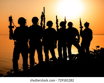 Army soldiers with rifles orange sunset silhouette