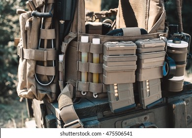 Army vest with a walkie-talkie, charged collars, stun grenades, luminous sticks, standing on a wooden box of ammunition.